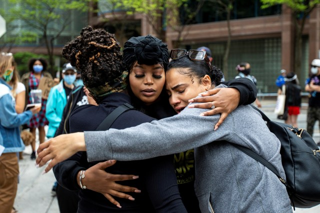 Patience Evbagharu (middle) hugs supporters outside Toronto Police headquarters as protesters march to highlight the deaths in the U.S. of Ahmaud Arbery, Breonna Taylor and George Floyd, and of Toronto's Regis Korchinski-Paquet, who died after falling from an apartment building while police officers were present, in Toronto, Ontario, Canada May 30, 2020. REUTERS/Carlos Osorio TPX IMAGES OF THE DAY
