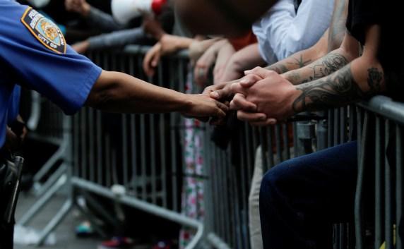 En contraste con la violencia de otras escenas, un policía estrecha la mano de un manifestante que está apoyado sobre una valla de contención en Brooklyn (REUTERS/Brendan McDermid)