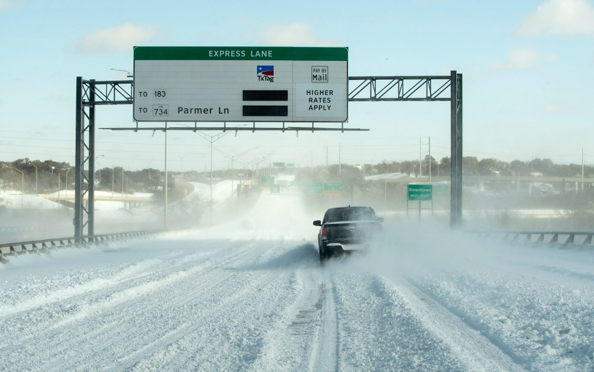 """A truck drives in the snow on a Texas highway. A toll road saying """"Express Lane to 183 to 737 Parmer Ln"""" appears above the road with its power out."""