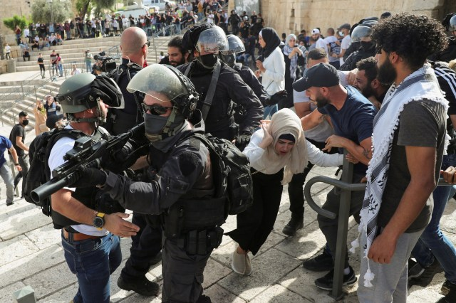 A Palestinian woman reacts during scuffles with Israeli security force members amid Israeli-Palestinian tension as Israel marks Jerusalem Day, near Damascus Gate just outside Jerusalem's Old City May 10, 2021. REUTERS/Ronen Zvulun