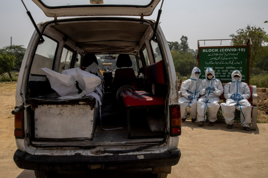 The body of a person, who died from the coronavirus disease (COVID-19), is seen inside an ambulance as healthcare workers wait for a grave to be prepared for its burial at a graveyard in New Delhi, India, April 28, 2021. REUTERS/Danish Siddiqui