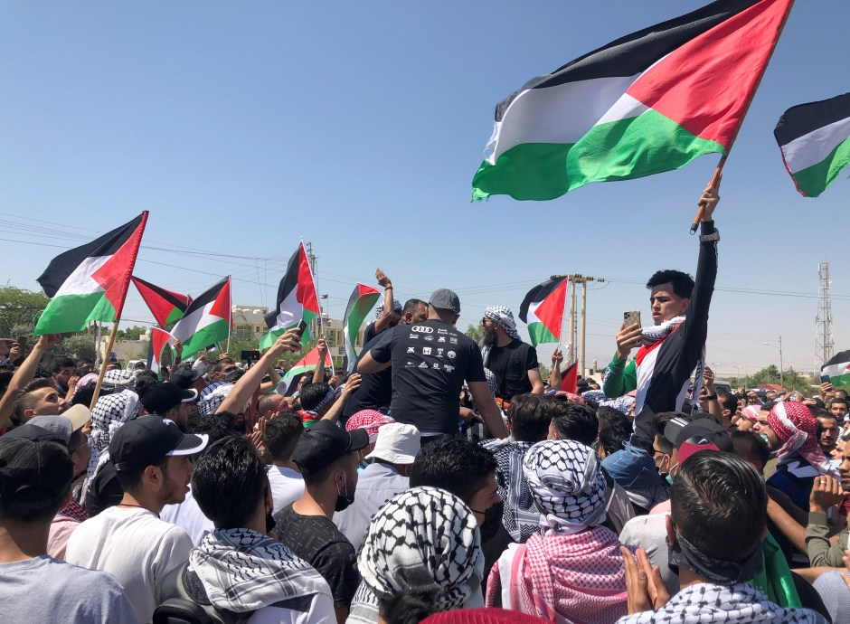 Demonstrators hold Palestinian flags during a protest to express solidarity with the Palestinian people, in Karameh, Jordan valley, Jordan May 14, 2021. REUTERS/Jehad Shelbak