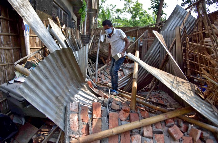 A man searches for his belongings amidst the debris after a boundary wall of his house collapsed following an earthquake in Nagaon district in the northeastern state of Assam, India, April 28, 2021. REUTERS/Anuwar Hazarika