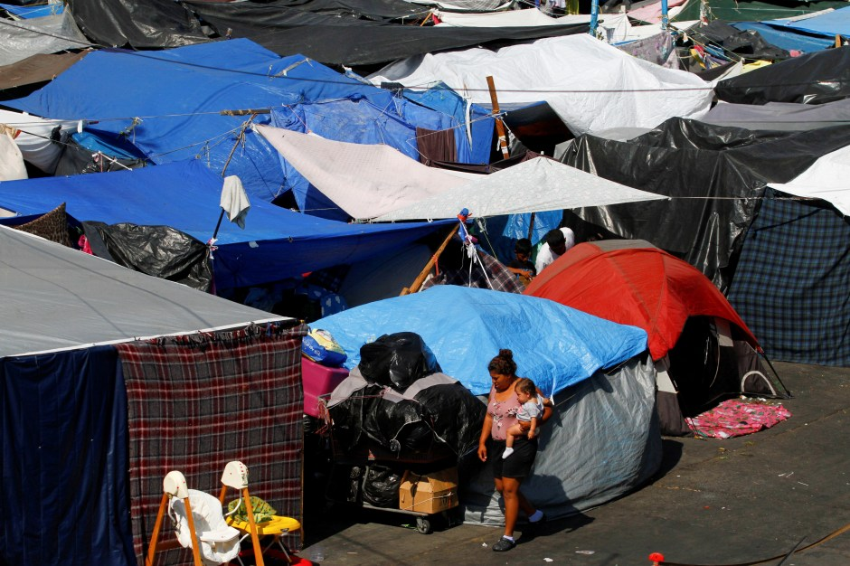 Asylum-seeking migrants are pictured at a makeshift camp after the U.S. Supreme Court ordered to uphold an immigration policy implemented under former President Donald Trump that forced thousands of asylum seekers to stay in Mexico to await U.S. hearings, at El Chaparral crossing port with the U.S., in Tijuana, Mexico August 25, 2021. REUTERS/Jorge Duenes