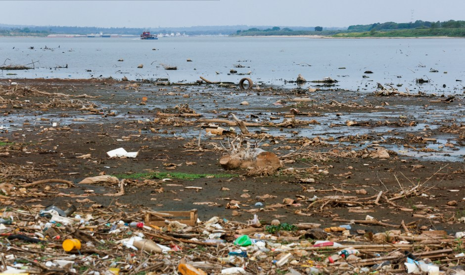 Garbage is pictured on the shore of the Rio Paraguay (Paraguay River), which flows down to the Parana River, as the lack of rain in Brazil, where the river originates, has brought water levels down, forcing cargo ships to reduce the amount of grains that are loaded for export, in Villeta, Paraguay August 24, 2021.  REUTERS/Cesar Olmedo