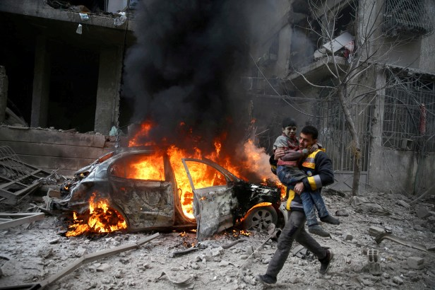 A Syrian Civil Defence member carries a wounded child in the besieged town of Hamoria, Eastern Ghouta, in Damascus, Syria January 6, 2018. REUTERS/ Bassam Khabieh/File Photo