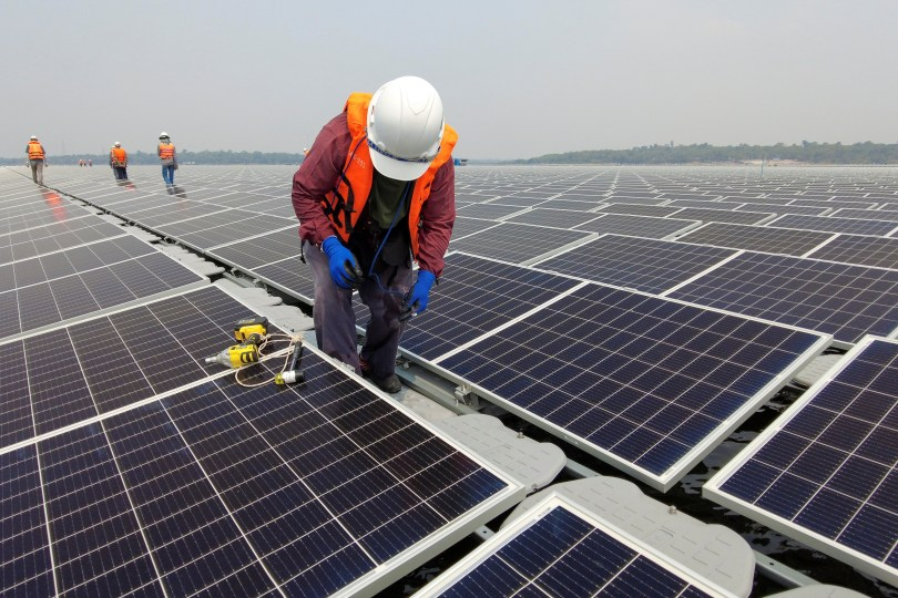 A worker stands between solar cell panels over the water surface of Sirindhorn Dam in Ubon Ratchathani, Thailand April 8, 2021. Picture taken April 8, 2021 with a drone. REUTERS/Prapan Chankaew