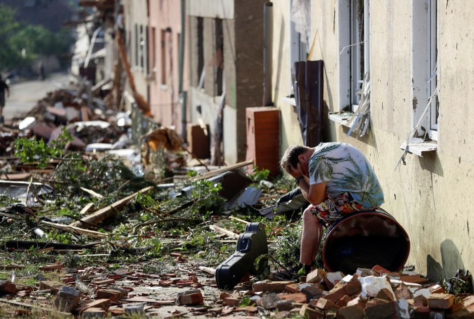 A man reacts outside damaged houses in the aftermath of a rare tornado that struck and destroyed parts of some towns, in Mikulcice village, Czech Republic, June 25, 2021. REUTERS/David W Cerny