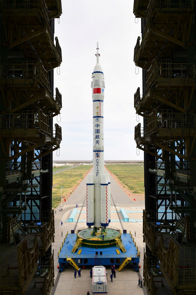 The Long March-2F Y12 rocket carrying the Shenzhou-12 spacecraft is transferred to the launch pad at Jiuquan Satellite Launch Center in Gansu province, China June 9, 2021. A three-man crew of astronauts is expected to board the spacecraft to Tianhe, the core module of China's space station.  Picture taken June 9, 2021. China Daily via REUTERS