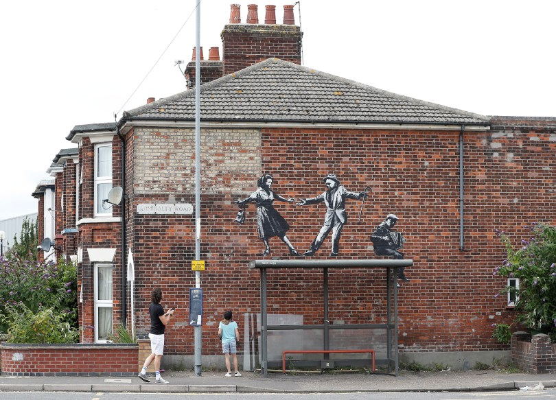 People stop to look at artwork created by Banksy in Great Yarmouth, Britain, August 8, 2021. REUTERS/Peter Nicholls