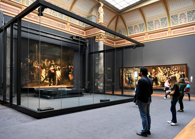 Poeple look at Rembrandt's famed Night Watch, which is back on display in what researchers say in its original size, with missing parts temporarily restored in an exhibition aided by artificial intelligence, at Rijksmuseum in Amsterdam, Netherlands June 23, 2021. REUTERS/Piroschka van de Wouw