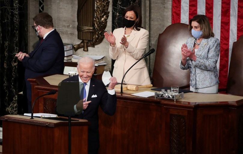 U.S. Vice president Kamala Harris and Speaker of the House Nancy Pelosi applaud as U.S. President Joe Biden arrives to deliver his first address to a joint session of Congress in the House chamber of the U.S. Capitol in Washington, U.S., April 28, 2021. Michael Reynolds/Pool via REUTERS
