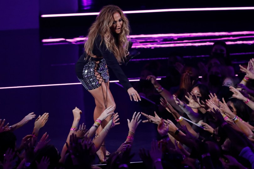 2021 MTV Video Music Awards - Show - Barclays Center, Brooklyn, New York, U.S., September 12, 2021 - Jennifer Lopez reaches out to audience members as she presents an award. REUTERS/Mario Anzuoni