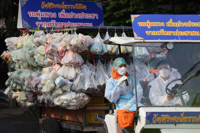 Buddhist monks and volunteers from Wat Siriphong Thamma Nimit temple wearing Personal Protective Equipment (PPE) ride a golf cart pulling a trailer truck loaded with bags of fresh vegetables to donating food and other necessities to vulnerable people whose livelihoods have been hit hard by the coronavirus disease (COVID-19) pandemic on the outskirts of Bangkok, Thailand, September 18, 2021. Picture taken September 18, 2021. REUTERS/Jiraporn Kuhakan