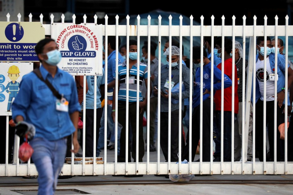 Workers wait in line to leave a Top Glove factory after their shifts in Klang, Malaysia December 7, 2020. Picture taken December 7, 2020. REUTERS/Lim Huey Teng - RC2ZLK9X2B1Q/File Photo