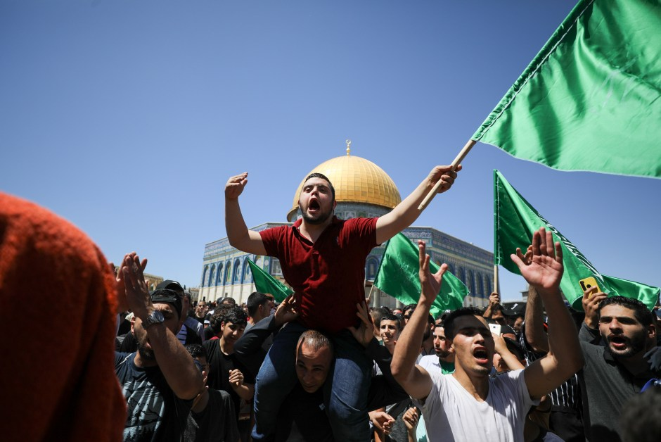 People hold Hamas flags as Palestinians gather after performing the last Friday of Ramadan to protest over the possible eviction of several Palestinian families from homes on land claimed by Jewish settlers in the Sheikh Jarrah neighbourhood, in Jerusalem's Old City, May 7, 2021. REUTERS/Ammar Awad