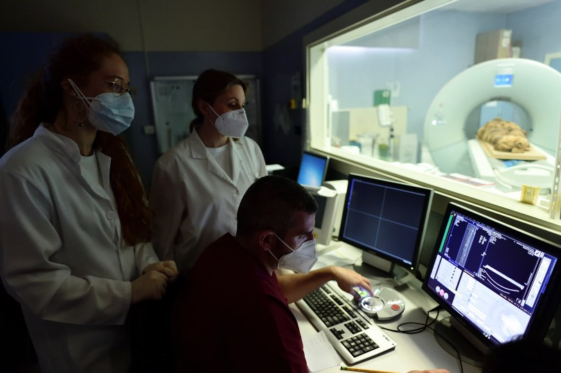 Medical radiology technicians and researchers look at a computer screen as an Egyptian mummy undergoes a CT scan in order for researchers to investigate its history at the Policlinico hospital in Milan, Italy, June 21, 2021. Picture taken June 21, 2021. REUTERS/Flavio Lo Scalzo