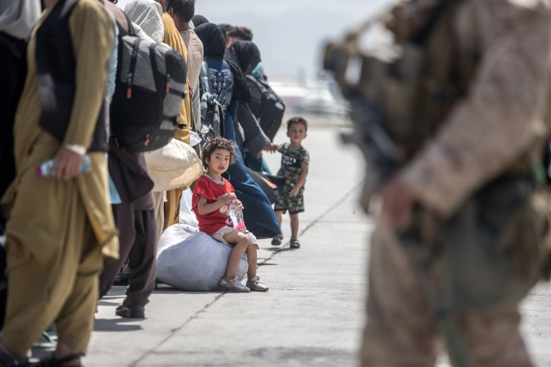 A child waits with her family to board a U.S. Air Force Boeing C-17 Globemaster III during an evacuation at Hamid Karzai International Airport, Afghanistan, August 22, 2021. U.S. Marine Corps/Sgt. Samuel Ruiz/Handout via REUTERS