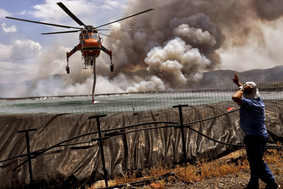 A helicopter is being filled up with water from a tank as a wildfire burns near the village of Spathovouni, near Corinth, Greece July 23, 2021. REUTERS/Vassilis Psomas