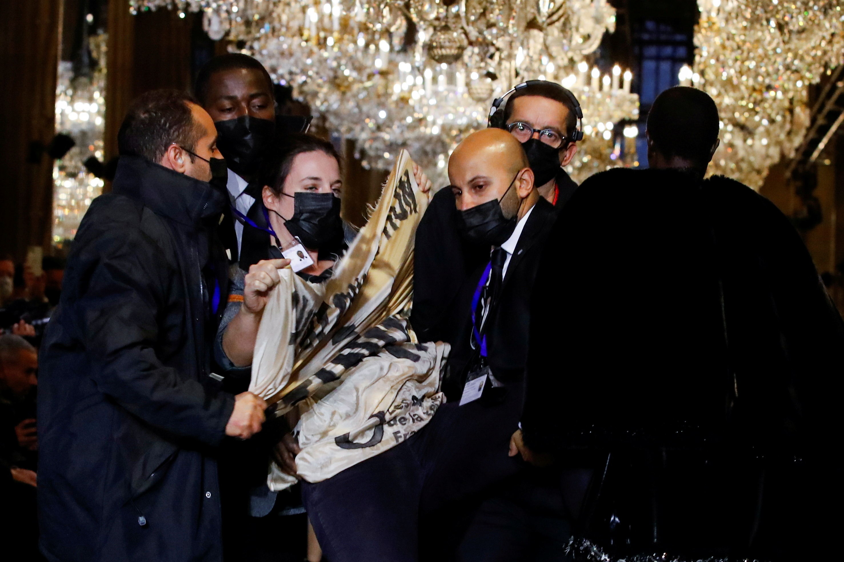Security personnel remove an activist belonging to the 'Les Amis de la Terre France' or 'Friends of the Earth - France' , who crashed the designer Nicolas Ghesquiere Spring/Summer 2022 women's ready-to-wear collection show for fashion house Louis Vuitton during Paris Fashion Week in Paris, France, October 5, 2021. REUTERS/Gonzalo Fuentes