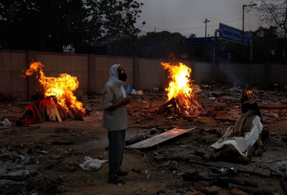 A man stands next to a funeral pyre of a relative who died from the coronavirus disease (COVID-19), during a mass cremation, at a crematorium in New Delhi, India May 1, 2021. REUTERS/Adnan Abidi