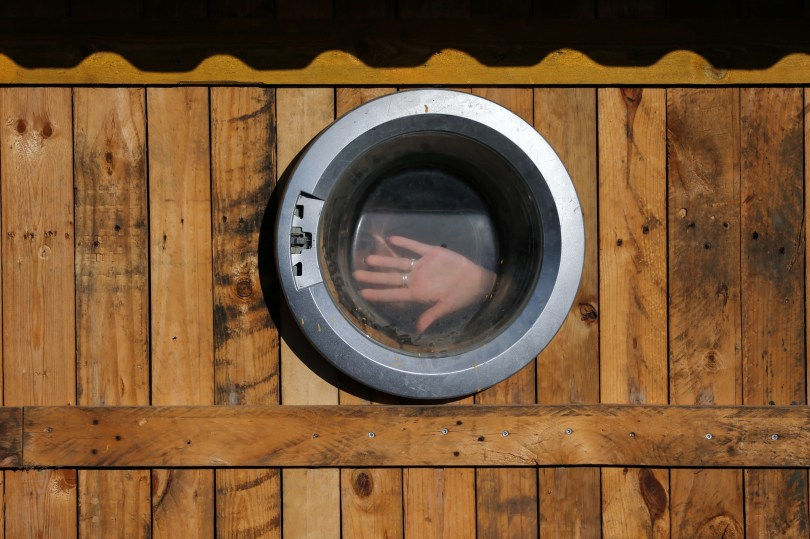 A hand of a Gaza woman is seen through a glass door of a washing machine that has been used as a window of a makeshift office at an environment-friendly beachfront cafe in Gaza July 8, 2021. REUTERS/Ibraheem Abu Mustafa