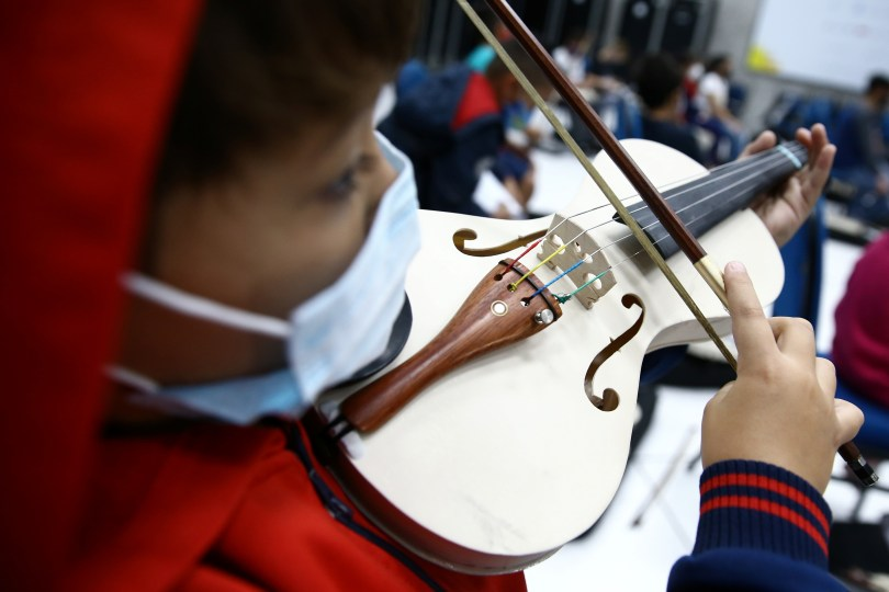A student plays a violin made from PVC piping at Locomotiva Project, a free music school for at-risk children in Santo Andre, Brazil September 8, 2021. REUTERS/Carla Carniel