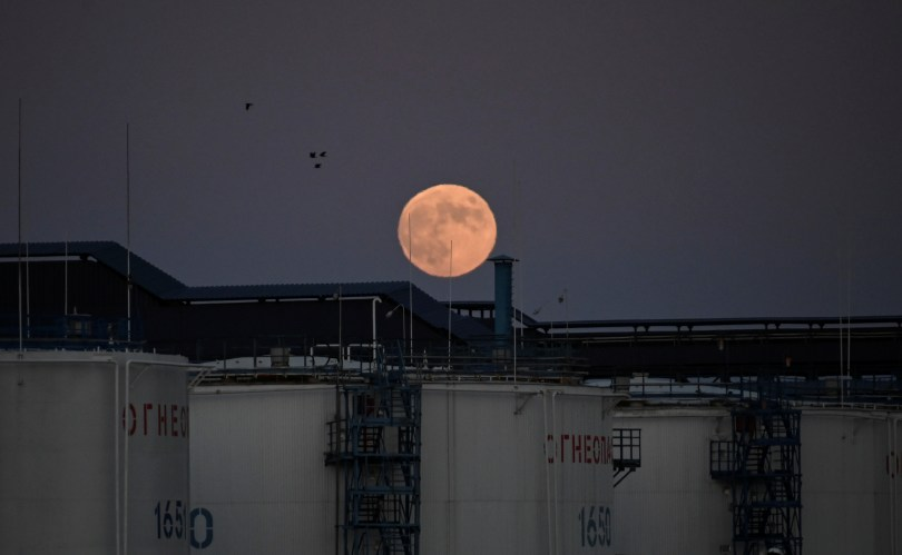 The moon rises behind the storage tanks of a local oil refinery in Omsk, Russia June 5, 2020. REUTERS/Alexey Malgavko