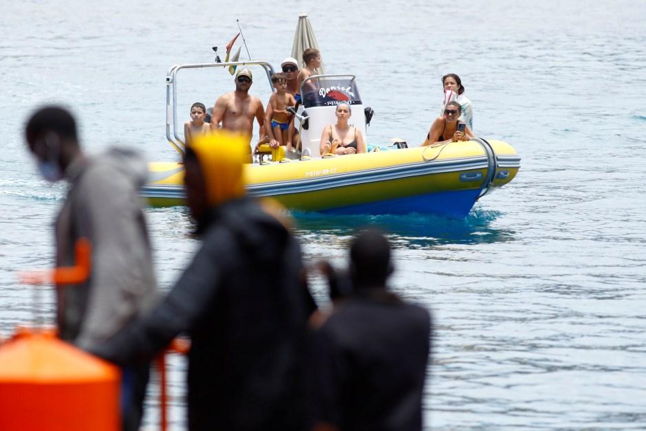 Un grupo de turistas en un barco observa a varios migrantes esperando para desembarcar de un buque guardacostas español, en el puerto de Arguineguín, en la isla de Gran Canaria, España el 20 de junio de 2021. REUTERS / Borja Suarez