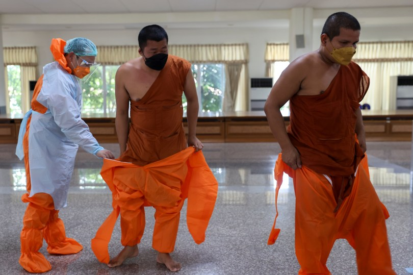 Buddhist monks from Wat Siriphong Thamma Nimit temple wear Personal Protective Equipment (PPE) in preparation before donating food and other necessities to vulnerable people whose livelihoods have been hit hard by the coronavirus disease (COVID-19) pandemic on the outskirts of Bangkok, Thailand, September 18, 2021. Picture taken September 18, 2021. REUTERS/Jiraporn Kuhakan