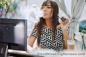 Woman vaping at computer - CloudNineEcigReviews