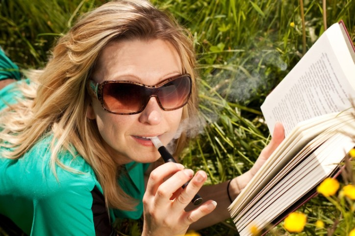 woman vaping in a park with a book