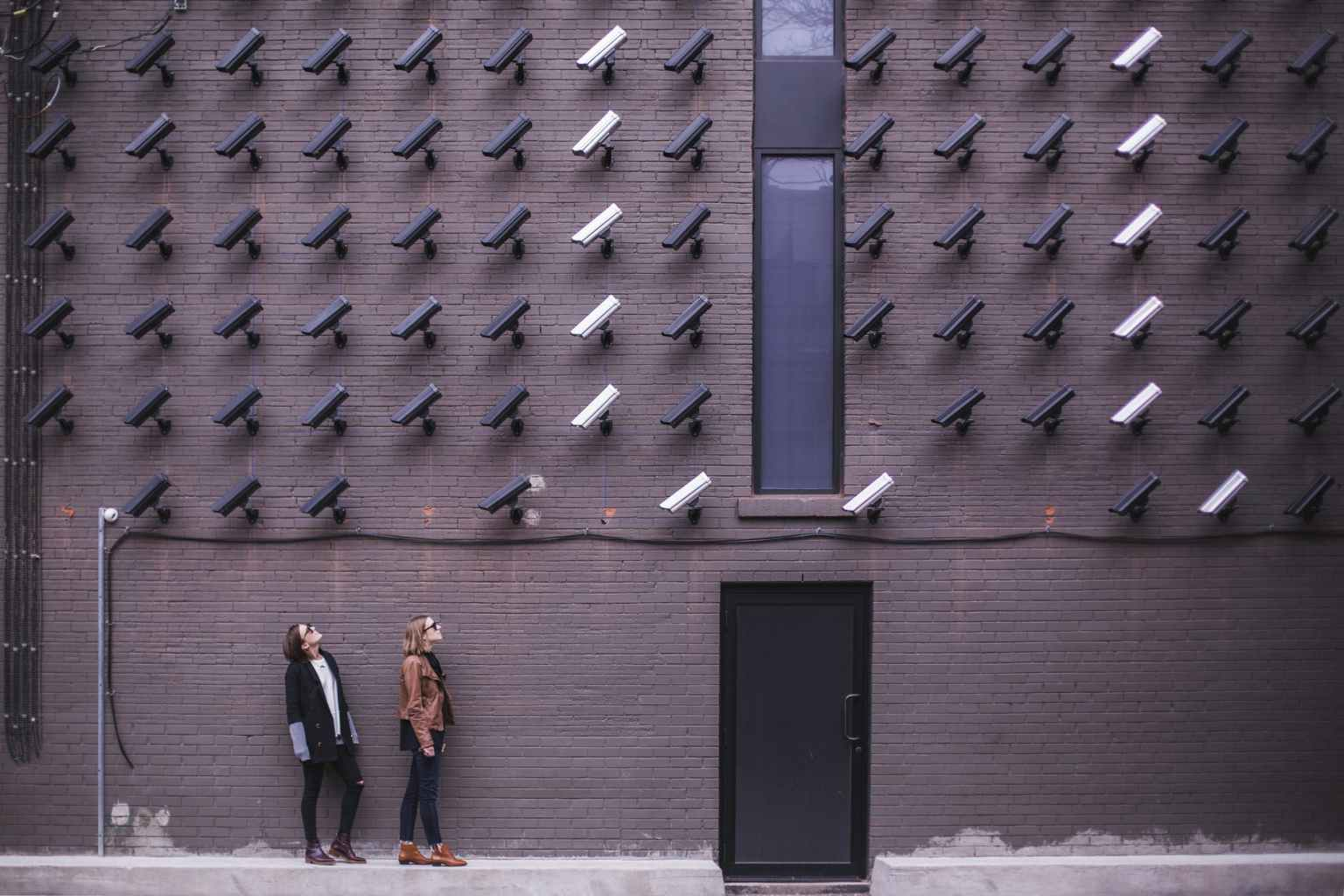 two person standing under lot of bullet cctv camera