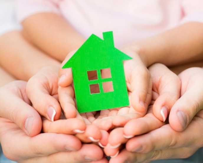 Family holding green paper house in hands. Real estate concept
