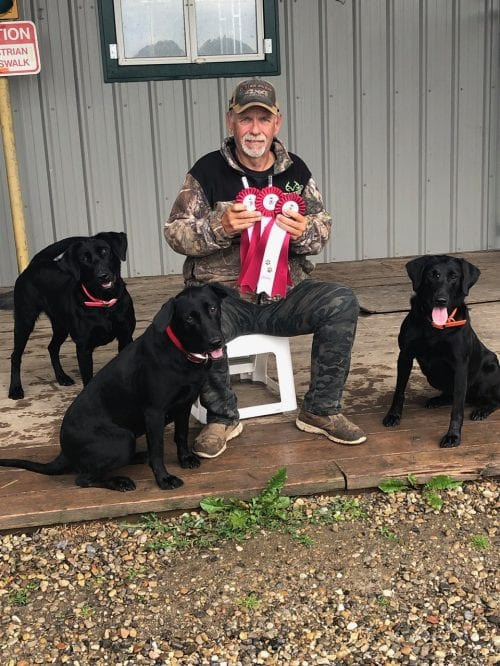Stu Mead sitting on deck with three award winning back Labrador Retrievers