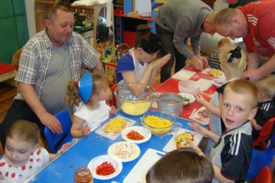 Children and their fathers making healthy Pizza's together.