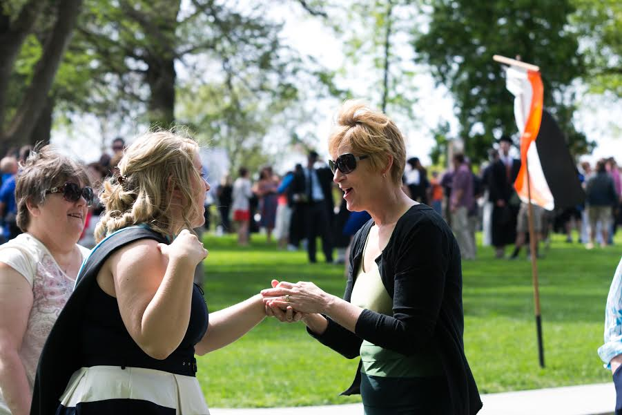 Laura Knobel with her mentor/second mom, Kim Jacobs, being congratulated on her masters degree while her biological mother looks on.