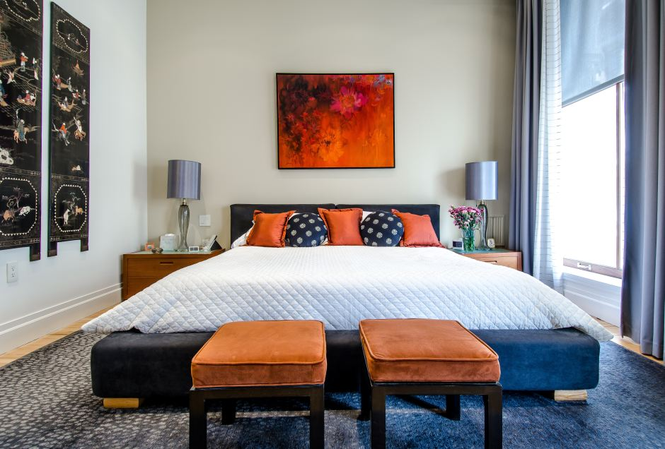 neat and tidy bedroom with orange throw pillows
