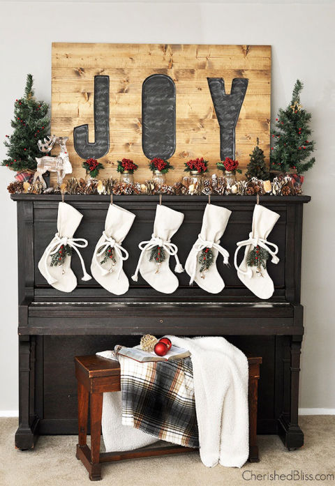 Okay, it's not a mantel, but this piano display is inspiring us to bust out our favorite Christmas carols. Mason jars stuffed with bright berries add just the right amount of festive color beneath an oversized wood sign. See more at Cherished Bliss.