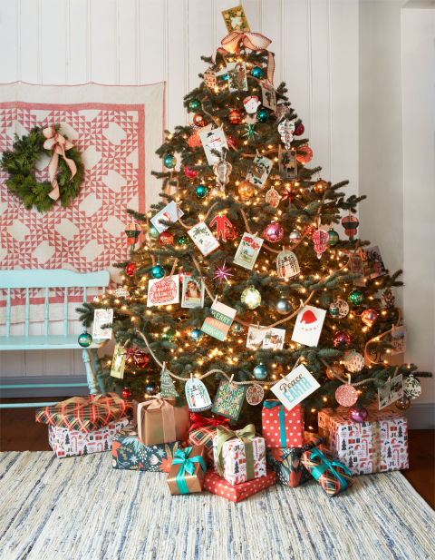 "Overflowing with good tidings, this ""friends and family"" tree features an assortment of holiday greeting cards (clipped to jute rope with mini clothespins) and a spirited mix of jewel-toned ornaments from the '50s and '60s."
