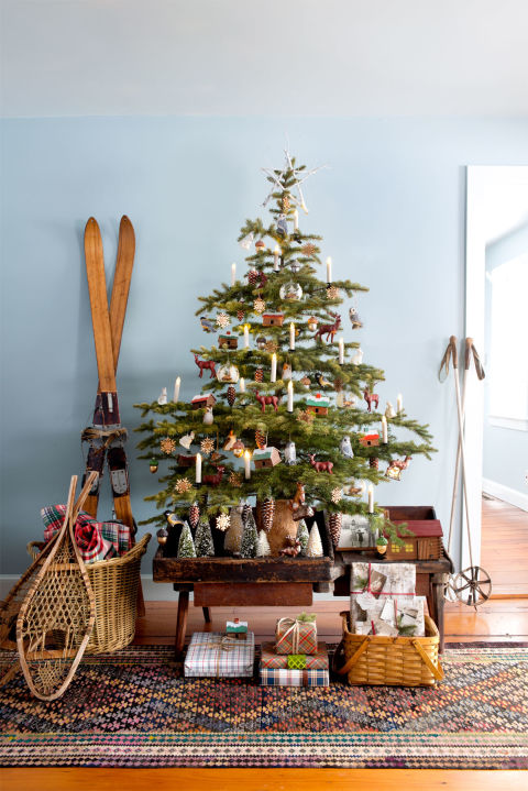 Wintry woodland frills (owl and deer ornaments, a forest of flocked bottle-brush trees in lieu of a skirt) evoke the snow-laden trek to grandmother's house, while flickering clip-on, battery-operated candles are reminiscent of the tapers in her windows. Antique snow shoes and skis reinforce the frosty feel. Get the look: vintage snowshoes ($50; ebay.com), bottle-brush trees ($16; amazon.com, battery-operated clip-on candles ($19; amazon.com), deer ornaments ($10; orientaltrading.com), owl ornaments ($14 for set of two; amazon.com)