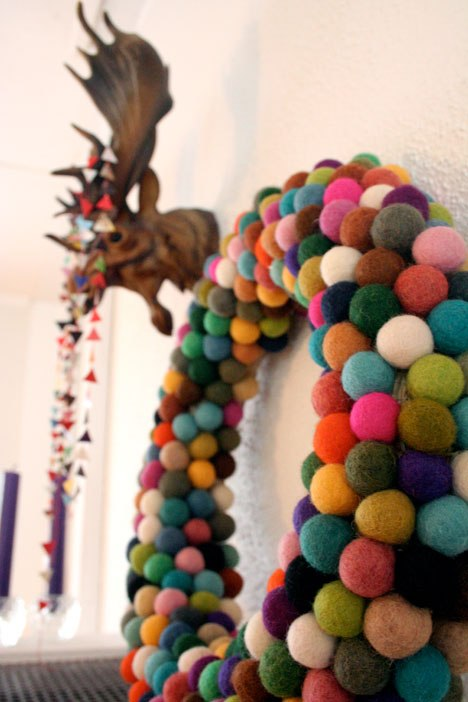Colorful felt balls combing to make the cutest wreath, perfect for a playroom. Get the full tutorial at Wonder How To.