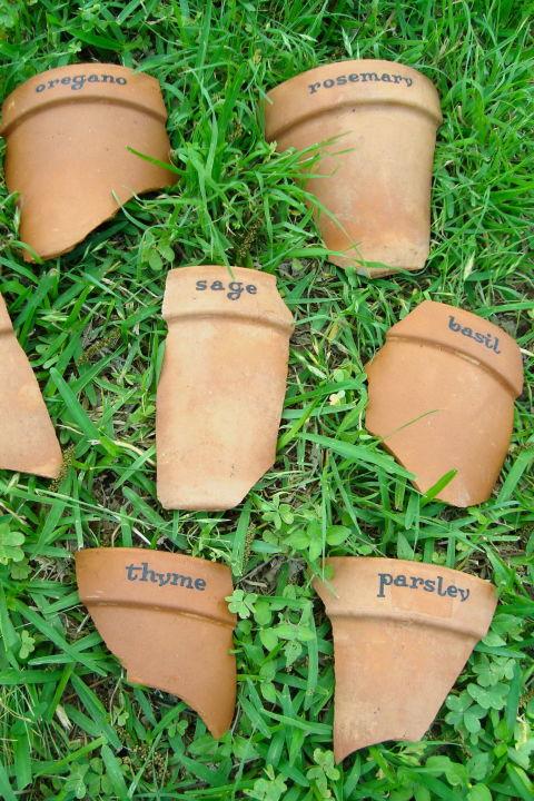 cocci di vasi di terracotta trasformati in etichette per le piante
