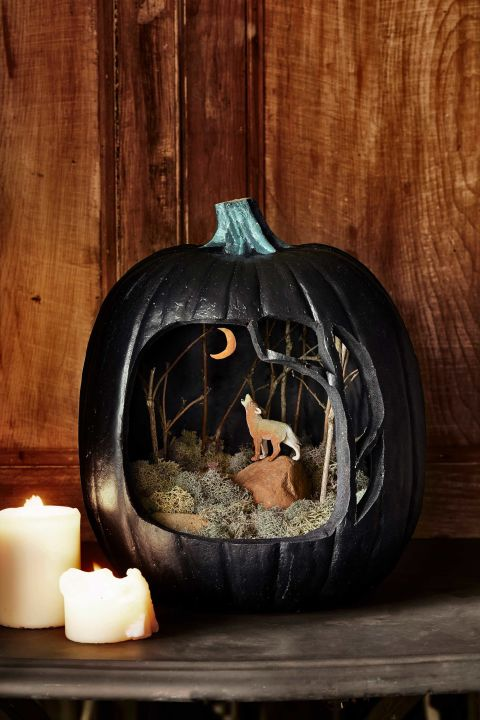 """This craft pairs materials from your own yard with an 11¼""""W x 14""""H black Funkin. To get started, print our carving templates; cut, as indicated, to create stencils for the tree-framed opening and moon at the back. With a felt-tip pen, trace the designs onto your Funkin, then carve. Spray-paint the Funkin's interior black (Krylon Colormaster, $6.49 for 12 oz.; amazon.com); let dry one hour. Place a green Styrofoam disk inside the faux pumpkin as a base. Using our photo as a guide, stick twigs into the base to form trees, then cover the base with moss ($16.92 for 8 oz.; amazon.com). Finally, hot-glue a wolf figurine to a rock, and set it and other rocks atop the moss (plastic wolf, $5; 1½""""L; amazon.com)."""
