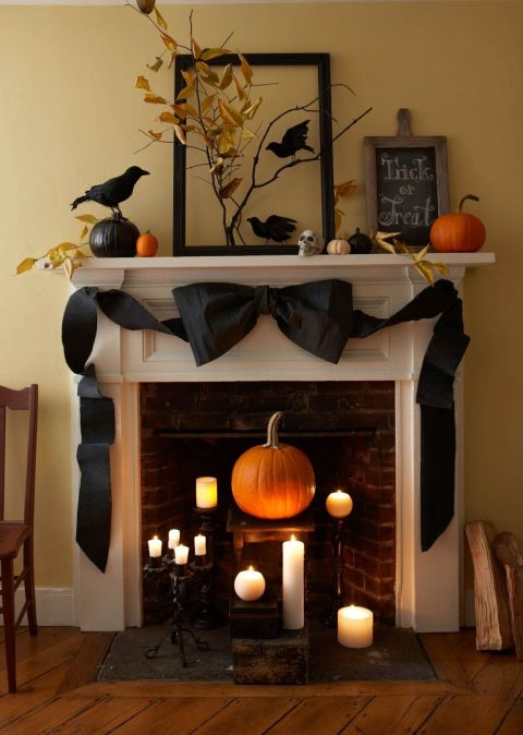 Add a high-low Halloween theme to your mantel with pumpkins, crows, and a crepe paper bow.  See more at Your Cozy Home.