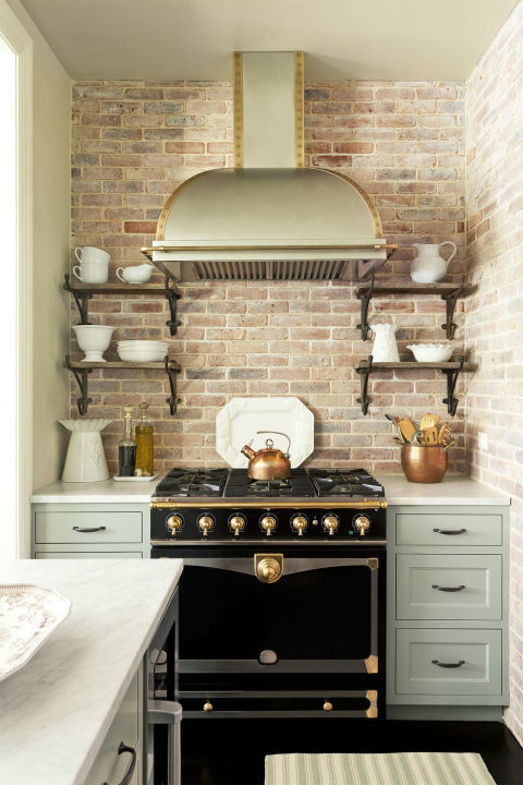 Brick is a timeless material with a homey, vintage feel. The warmth of this brick backsplash emulates the hearth-like stove. The rich color tones work to blend the cream cabinetry with the dark wood trim.