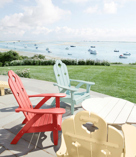 Colorful Adirondack chairs from Charleston Gardens brighten this beach house's terrace.