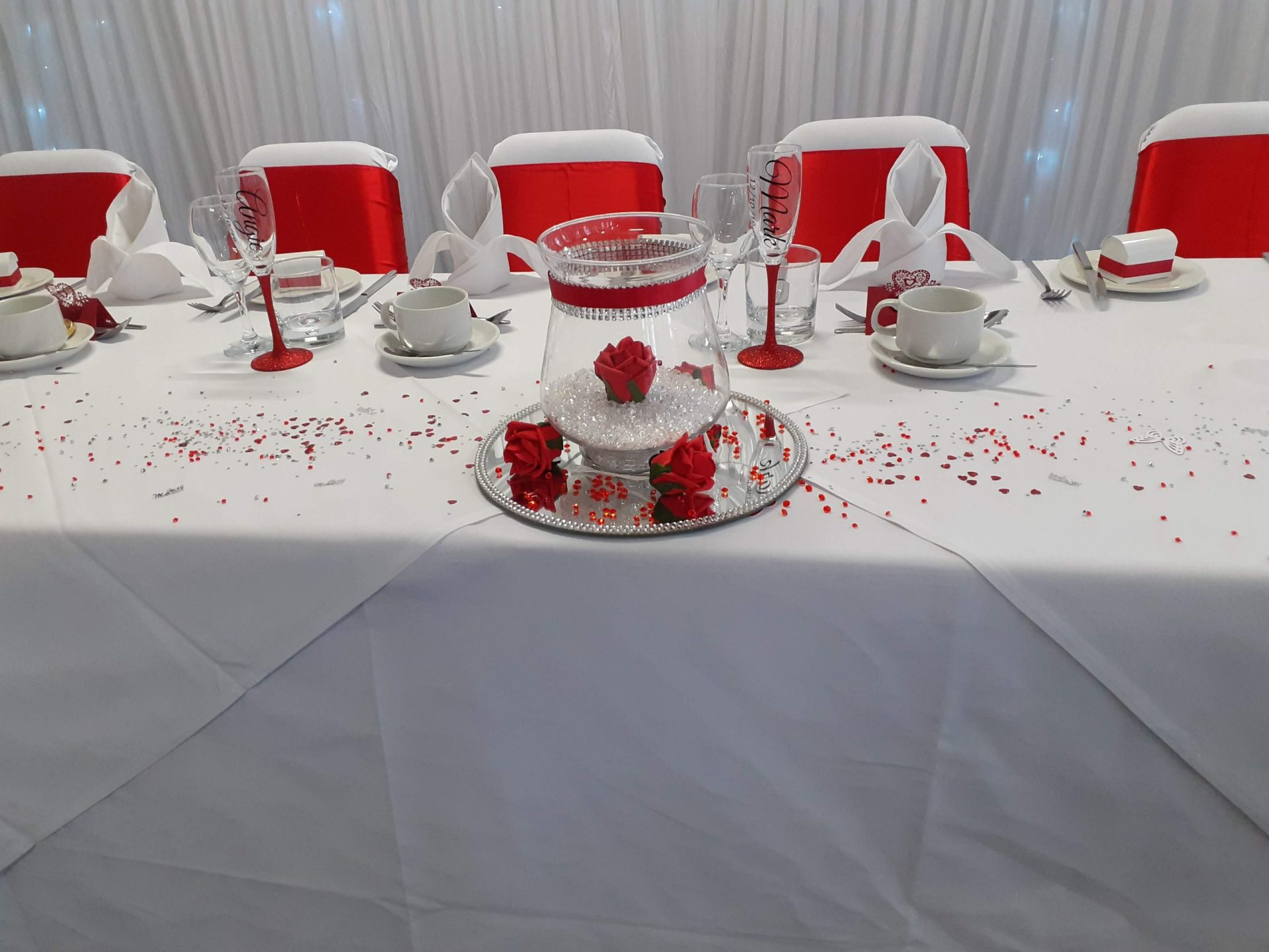Red themed wedding with sashes and Glass table centers