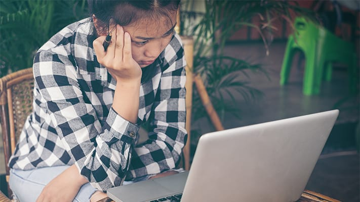 Girl slouched over computer in coffee shop looking frustrated