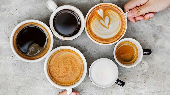 6 cups of coffee on a table, all containing different levels of creamer and darkness